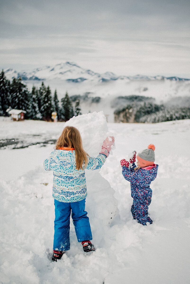 photoshoot for a family two girls playing with a snowman in Avoriaz (French Alps) on their ski holiday
