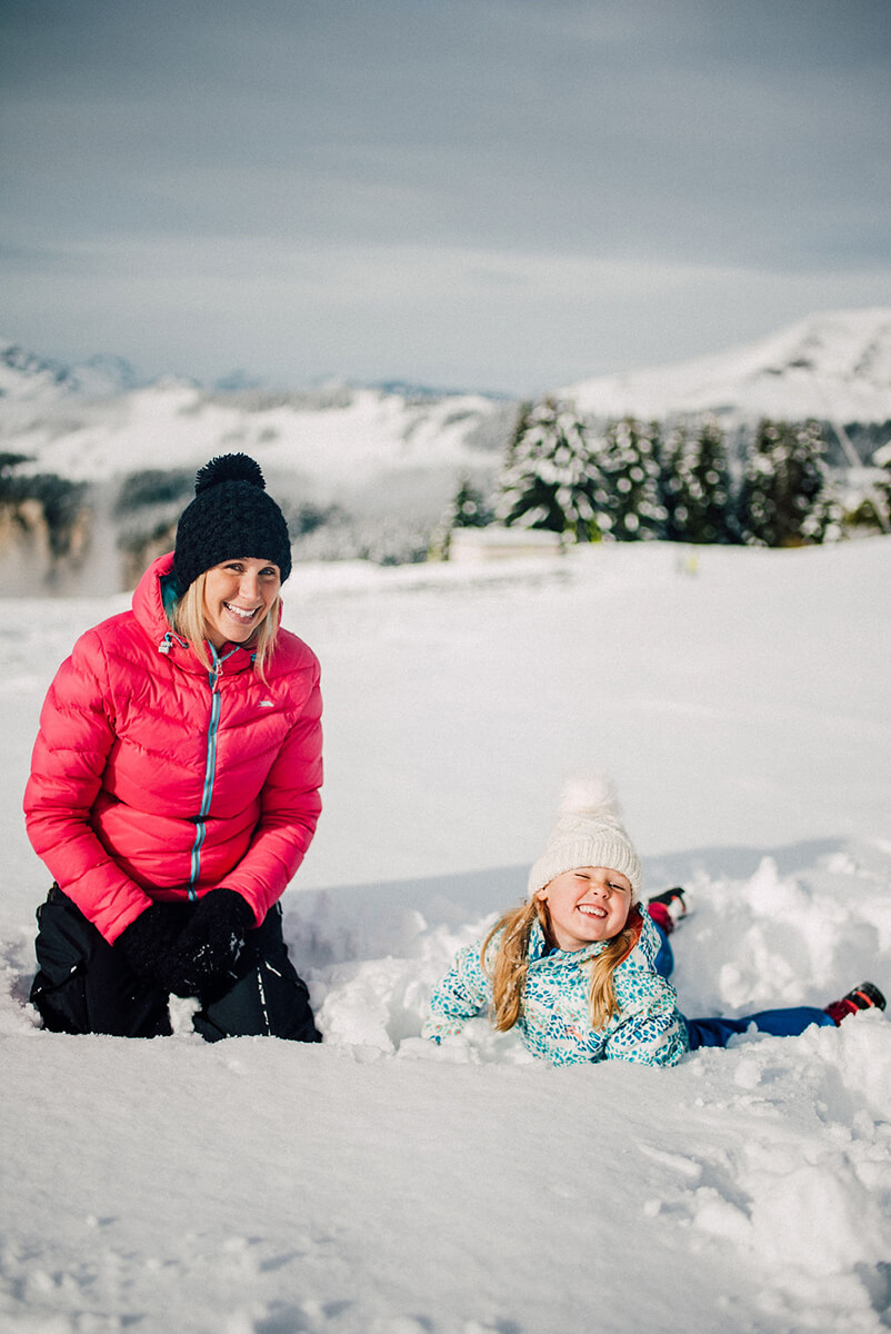 photoshoot for a family mom and daughter playing with a snowman in Avoriaz (French Alps) on their ski holiday