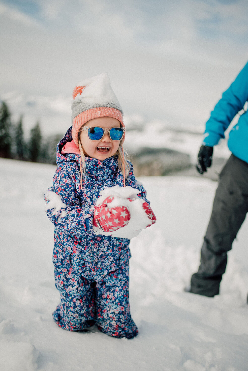 cute kid with a snowball and sun glasses at Avoriaz, French Alps