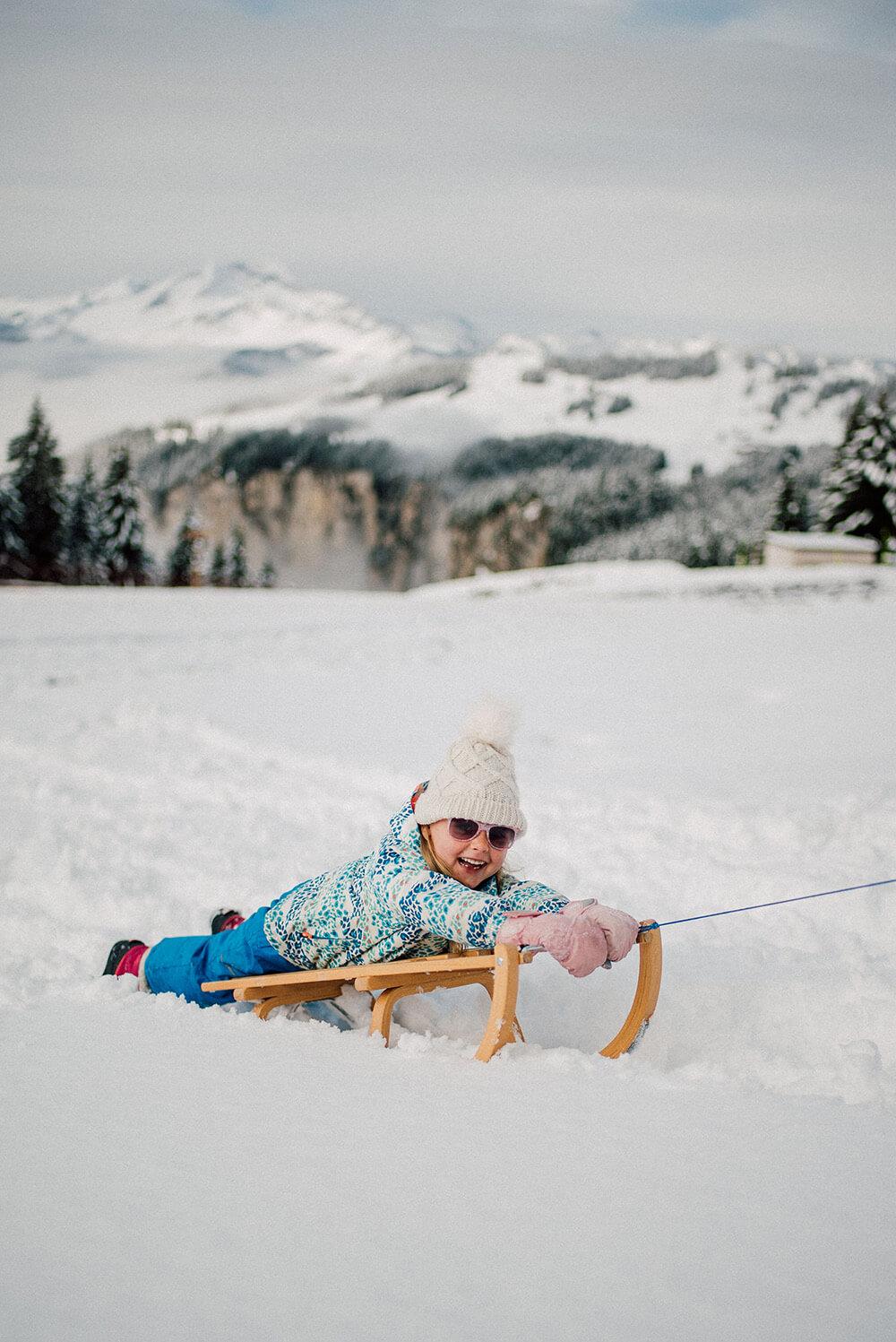 kid on a sledge having fun in snowy avoriaz
